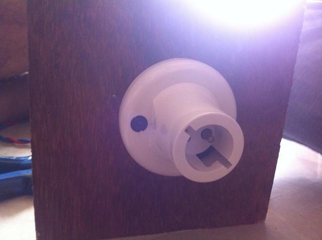 Perforar en el centro de un cuadrado que ya hemos cortado. Pase los cables por el agujero y fijarlos con portalámparas. Y luego fijar el portalámparas a la madera contrachapada con tornillos.