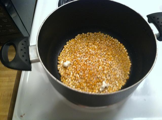 Una vez que los dos primeros núcleos pop sabes el aceite está suficientemente caliente como para añadir el resto de las palomitas de maíz sobre dos tazas debería ser suficiente para hacer un gran tazón de palomitas de maíz.