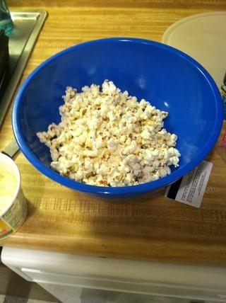Vierta la mantequilla a las palomitas de maíz de un medio a la vez que permite suficiente espacio en el recipiente para sacudir y distribuir la mantequilla en todas partes. Luego agregue la cantidad deseada de sal.