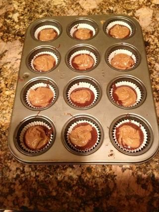 Coge una cucharadita colmada de la mezcla de mantequilla de maní y rodar en un punto y pelota. Aplanar ligeramente. Soltarlo en el medio de la chocolate.