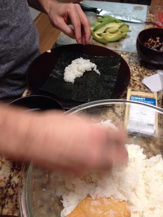 Ahora coloque una hoja de nori lado brillante hacia abajo y cubrir con una fina capa de arroz