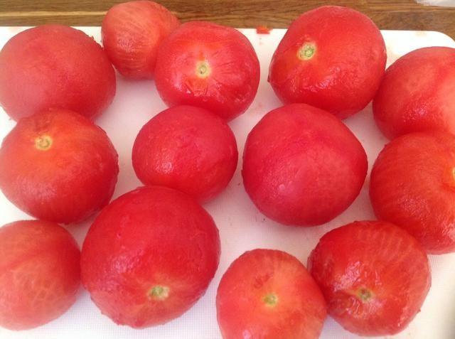 Pelar los tomates, ya que estaban descansando en agua hirviendo, las pieles deben salir muy fácilmente.