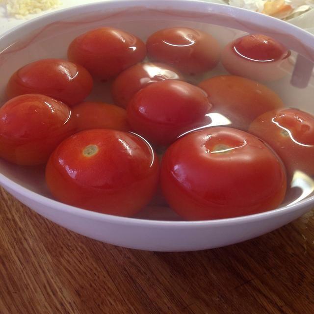 Mientras que la cebolla, el ajo y los pimientos están desacelerando cocinar, poner los tomates en un bol grande y llenarlo con agua hirviendo.