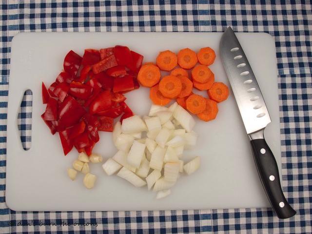 Alrededor de cortar la cebolla, el pimiento, la zanahoria y el ajo.