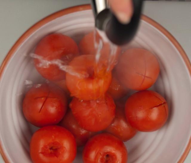 Coloque los tomates en un tazón grande o cacerola y cubrir completamente con agua hirviendo.