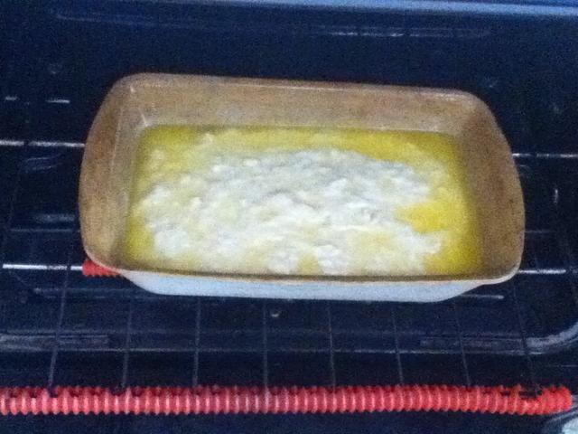 Extender la masa uniformemente en el molde preparado, de manera uniforme vierta la mantequilla derretida sobre la parte superior.