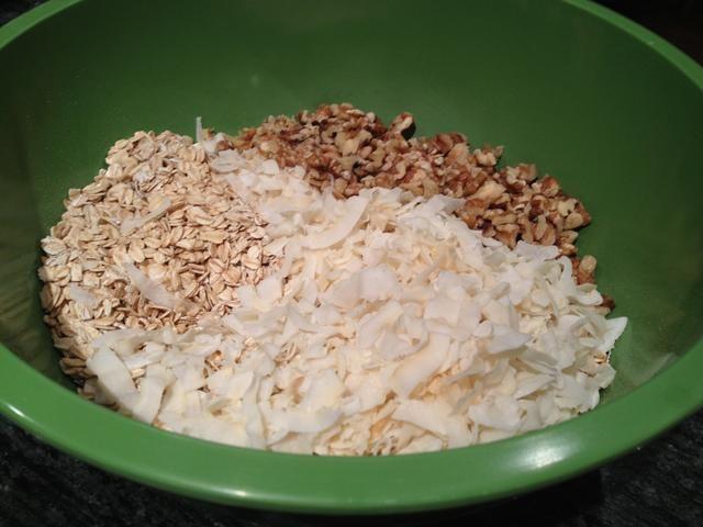 En un tazón grande, combine la avena, coco rallado y las nueces picadas.