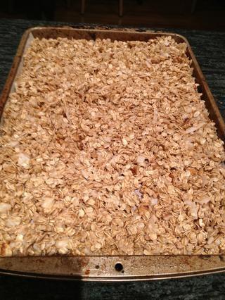 Coloque un pedazo de papel de pergamino en una bandeja para hornear. Corre la granola en la parte superior.