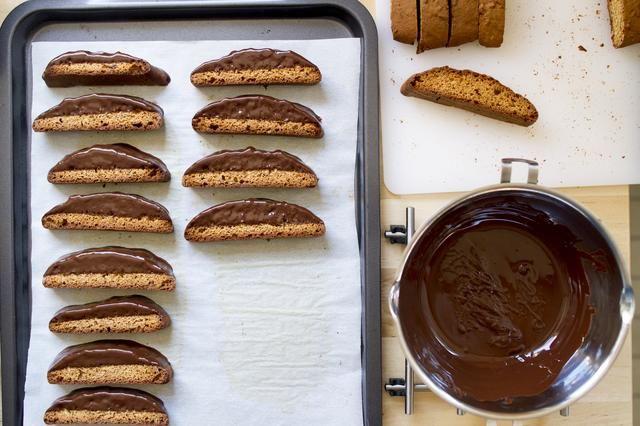 Derretir el chocolate negro al baño maría. Sumerja ½ de cada biscotti en el chocolate derretido, agitando el horno ligeramente para eliminar el exceso de chocolate.