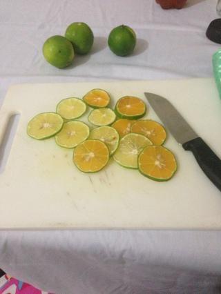 Cortar los limones (limas) a rodajas finas