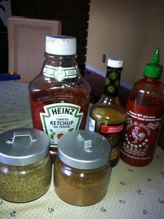 Combine la salsa de tomate, salsa de ostras, salsa picante Sriracha, chile en polvo y el orégano en un tazón.