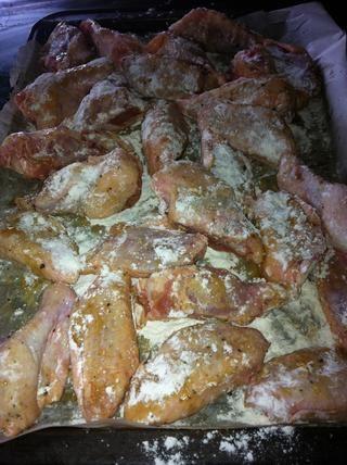 Ligeramente el polvo de las alas de pollo con harina, para crear una capa crujiente