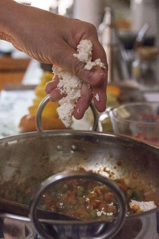 Añadir en el queso Paneer desmenuzado y media taza de agua.