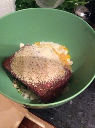 Agregue la carne, el pan rallado, el perejil, la cebolla, el ajo, el queso, la pimienta, la sal, la nuez moscada, y el huevo.