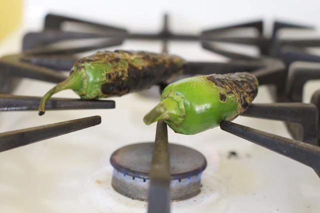 Asar los chiles jalapeños directamente en su tapa de la estufa de gas o en su parrilla, hasta que son carbonizados en todos los lados.
