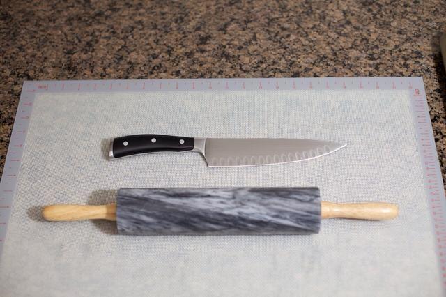 Mientras la masa está aumentando, consigue su rodillo y cuchillo listo. Ruedo la masa sobre una esterilla de silicona para que pueda cortar directamente sobre ella.