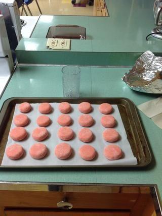 Con una taza aplanar las bolas de masa y luego ponerlas en el horno