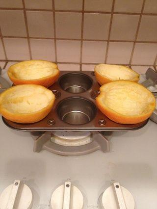 Pon las naranjas en el molde para muffins para que se sientan en posición vertical.