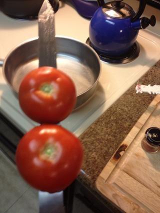 Apuñalar a un par de tomates. Usted puede agregar una cebolla también. Obtener estos en la parrilla primero y cocinar durante unos 10 minutos y luego terminar en un horno caliente durante otros 7-10 minutos hasta que estén blandas.
