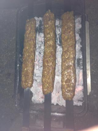 Una vez que el carbón está en gris sobre poner en carne. Apriete los extremos una vez más para asegurar que los kebab don