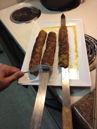 Después de 10 minutos, retire kebab de la parrilla y tire de carne de pincho con un tenedor para mantener la carne en su lugar y deslice el pincho.