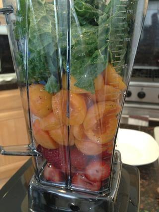 Coloque las fresas, albaricoques y la col rizada en la licuadora.