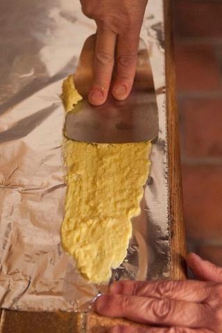 Tome una espátula plana filo y difundir la tira de masa por el papel de aluminio, casi como si estuviera enyesado de una pared.
