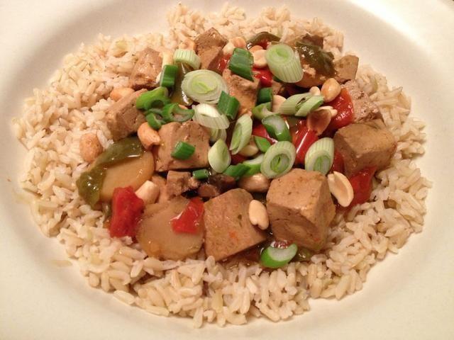 Servir el tofu en una cama de arroz integral. Espolvorear un poco de aceite de sésamo en la parte superior, seguido de los cacahuetes y las cebolletas. ¡Disfrutar!