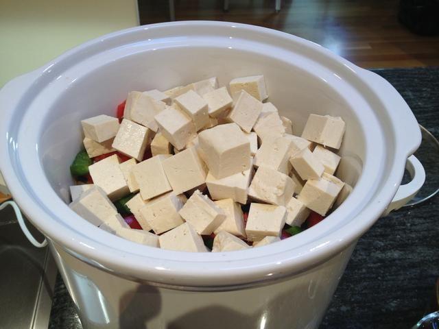 Cortar el queso de soja y las castañas de agua y añadir a la olla de cocción lenta.