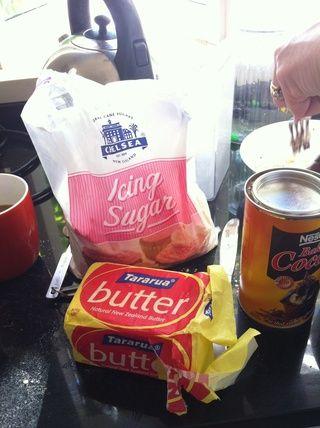 Ahora, para la formación de hielo. Coloque el azúcar en polvo, cacao en polvo, la mantequilla y la leche en un recipiente resistente al calor sobre un cazo de agua hirviendo.