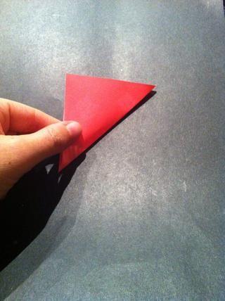 Doble la esquina inferior derecha en la esquina superior izquierda, creando un triángulo. Pase su uña en la parte inferior de la tapa.