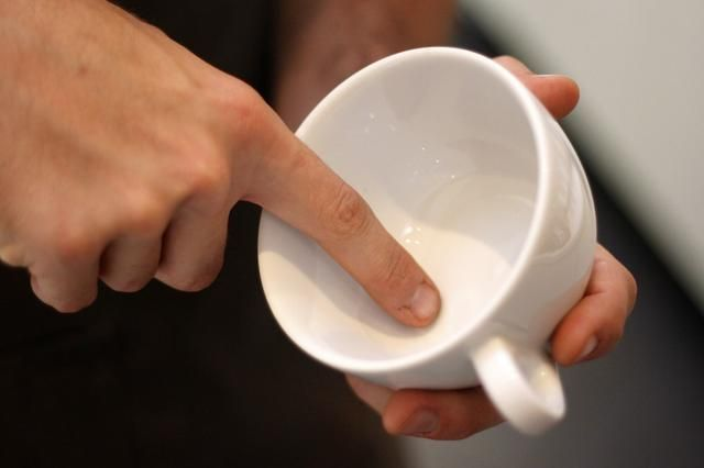 Cuando se inicia el arte latte, que'll want to tilt your cup to the side and hit this area right here with your foam from high up.