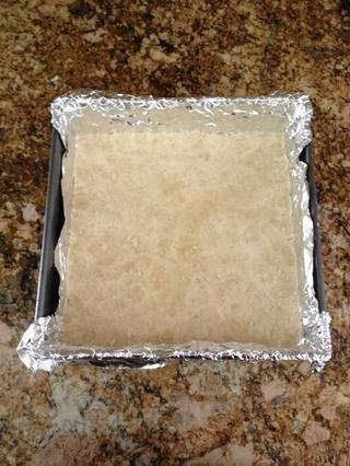 Preparar un molde cuadrado de 8 pulgadas con forro de papel de aluminio, asegurándose de que al menos uno voladizos pulgadas a cada lado. Uniformemente espolvorear la mezcla en el fondo de la sartén y presione con los dedos.