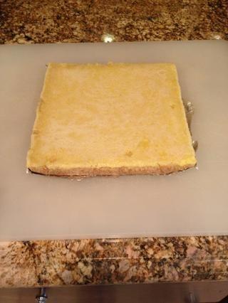 Transferir el molde a una rejilla hasta que se enfríe por completo. Levante la lámina de la sartén sobre una tabla de cortar.