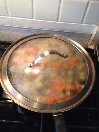 Añadir un chorrito de agua y cubrir el permiso mezcla de media / alta. Permita que las verduras para cocinar durante 5 minutos. Luego remover y dejar cocer durante 5 minutos más o hasta que las verduras se ablanden.