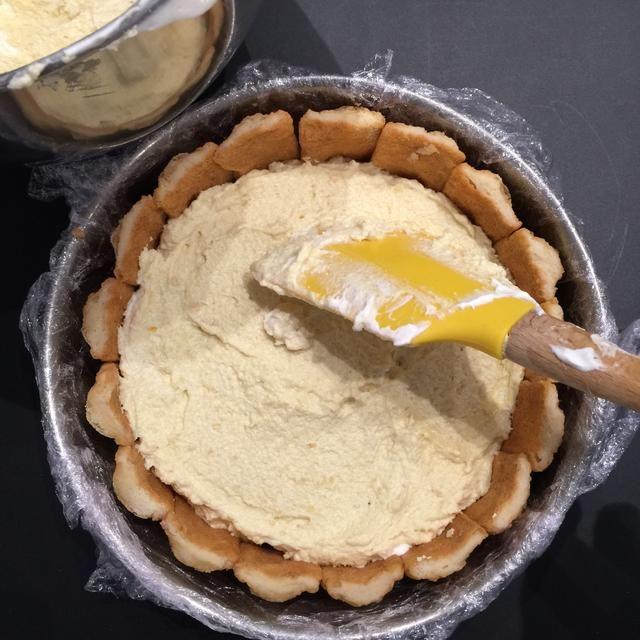 Ponga la mitad de la crema. Cubra con una capa de galletas bañadas en el zumo de naranja