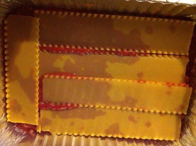 Añadir una capa de lasaña sin cocer.
