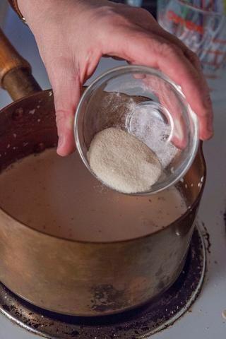 Esparce la gelatina o agar agar en la parte superior de la leche o crema. Deje que la gelatina se sienta allí durante unos 2 minutos para que se