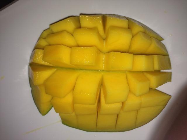 Cortar 2 mangos. De esta manera atajo de cortar los mangos en cubos pequeños. Recogí la pulpa del mango con una cuchara.