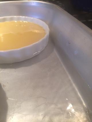 Agregar suficiente agua caliente a la sartén para llegar a la mitad de la altura del plato de natillas.