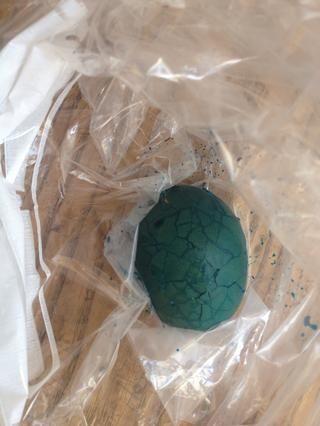 Coloca el huevo en el pozo bolso y abrigo con el colorante de alimentos.