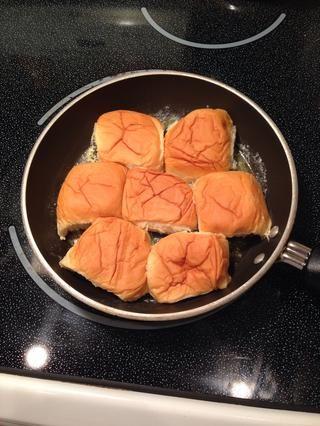 Reduzca sus rollos por la mitad y poner las tapas en la sartén la mantequilla.