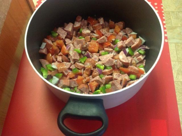Combine la salchicha y verduras frescas. Ligeramente saltear. Añadir ingredientes enlatados + frijoles fuego lento.