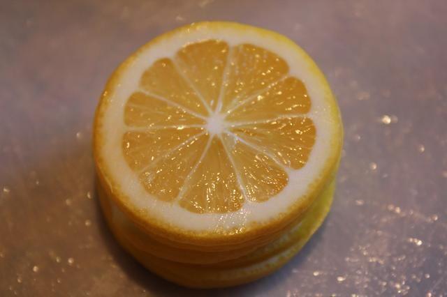 El uso de una mandolina o un cuchillo afilado, cortar los limones transversalmente en rodajas finas, desechando las semillas a medida que avanza.