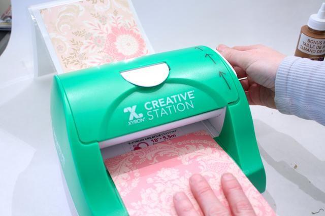 Puede pegar el papel con pegamento pegajoso, pero recomiendo esta pequeña máquina dulce la Estación Creativa Xyron 5 pulgadas. Si gluing- pegue el rodillo primero y luego añadir el papel