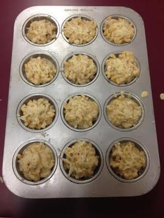 Tome la pasta y poner en cada uno de los moldes para muffins. A continuación, agregue el resto del queso a la parte superior de cada panecillo.