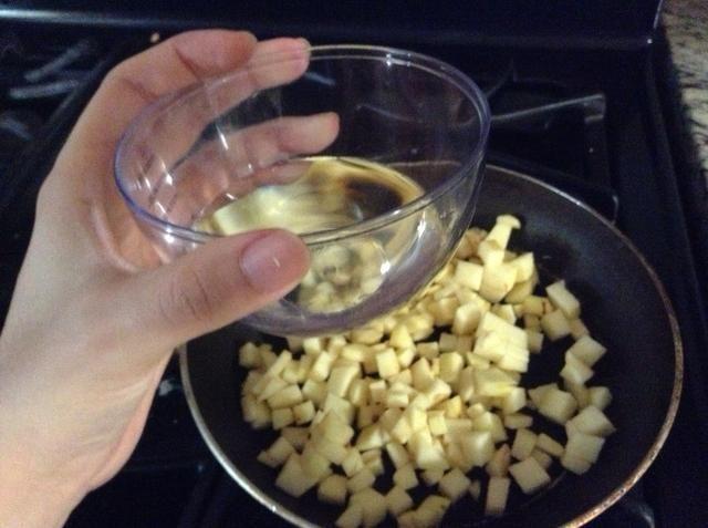 Ponga las manzanas cortadas en la sartén a fuego medio y añadir un poco de agua.