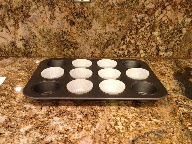 Forrar un molde de la magdalena con tazas de papel para hornear.