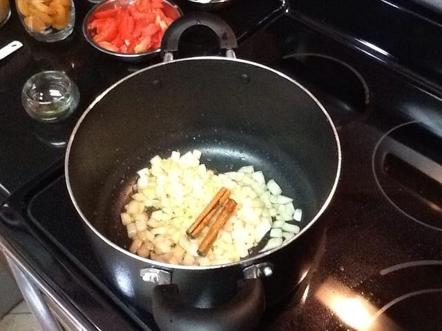 Añadir 2 cucharadas de aceite, el calor y luego agregar las cebollas, los palitos de canela de Ceilán y el jengibre y saltee durante 5 minutos o hasta que las cebollas estén suaves.