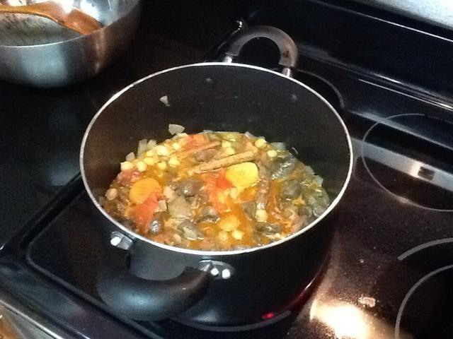 Una vez que los caldos comienza burbujeantes añadir el cordero frito, cubrir con una tapa y cocinar por una hora. Revuelva de vez en cuando y añadir media taza de agua si quieres más salsa en el plato.